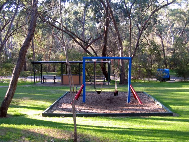 A swing set surrounded by bright grass beneath a native canopy at the Belair National Park Holiday Park